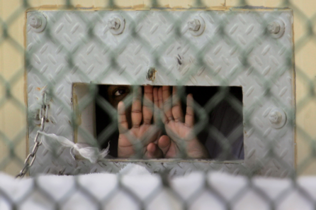 "A detainee shields his face as he peers out through the so-called ""bean hole"" which is used to pass food and other items into detainee cells, at Camp Delta detention center, Guantanamo Bay U.S. Naval Base, Cuba, Monday, Dec. 4, 2006."