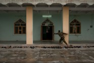 Shedding his sandals, a Sunni Afghan National Army soldier strides across a row of footwear and through the screen door of a crowded mosque during the sunset Magrib prayer in Mehtarlam district, Laghman province