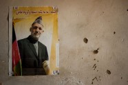 Craters of chipped plaster surround a poster of Afghan President Hamid Karzai on a wall in Mehtarlam district, Laghman province