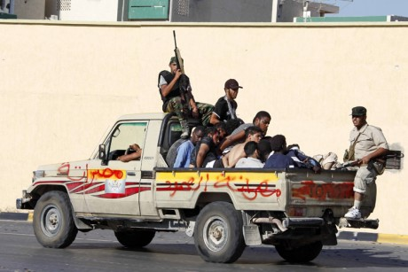 "1225e3305 Libyan rebels secure prisoners in the back of a pick-up truck. The graffiti  on the truck, in Arabic, reads, ""Misrata steadfastness."" (Credit: AP)"