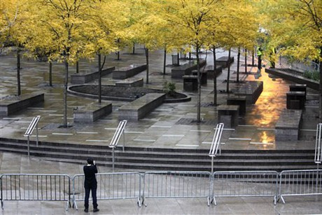 A pedestrian takes a picture of an empty and closed Zuccotti Park in New York, Tuesday, Nov. 15, 2011.