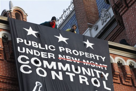 A group of protesters inspired by Occupy D.C. protest hang a banner on Franklin School building, in Washington, Saturday, Nov., 19, 2011