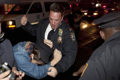 An Occupy Wall Street protestor draws contact from a police officer near Zuccotti Park after being ordered to leave the longtime encampment in New York, Tuesday, Nov. 15, 2011
