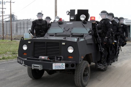 Police in riot gear move to another location at the port facilities in Longview, Wash., Wednesday, Sept. 21, 2011.