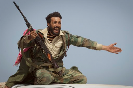 In this March 29, 2011 file photo, a Libyan rebel urges people to leave, as shelling from Gadhafi's forces started landing on the frontline outside of Bin Jawaad, 150 km east of Sirte, central Libya. (AP Photo/Anja Niedringhaus, File)