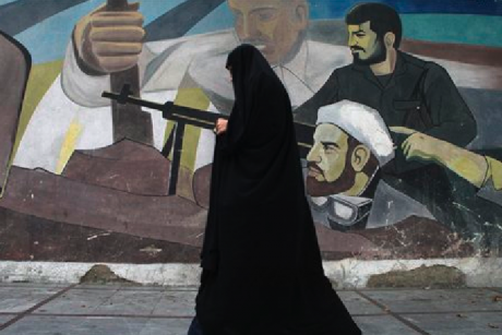 In this Tuesday, Oct. 18, 2011 photo, an Iranian woman walks past a mural depicting members of Basij paramilitary force, portraying Iranians' solidarity against their enemies, in Tehran, Iran.
