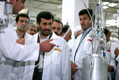 In this April 8, 2008, photo released by the Iranian President's Office, Iranian President Mahmoud Ahmadinejad, center, listens to a technician during his visit of the Natanz Uranium Enrichment Facility.
