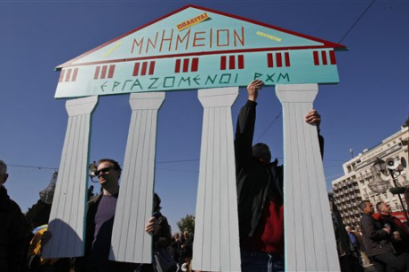 Employees of the Byzantine and Christianity museum hold a cardboard replica of ancient ruins which reads: ''Monument for sale'' during a peaceful protest outside the Greek Parliament in Athens, Sunday, Feb. 19, 2012