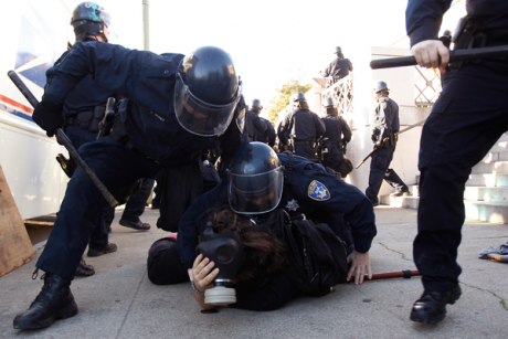 Members of the Oakland Police Department arrest an Occupy Oakland demonstrator in Downtown Oakland, California January 28, 2012