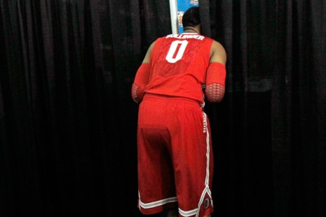 Ohio State forward Jared Sullinger peeks through a curtain while teammates participate in interviews in New Orleans on March 29.