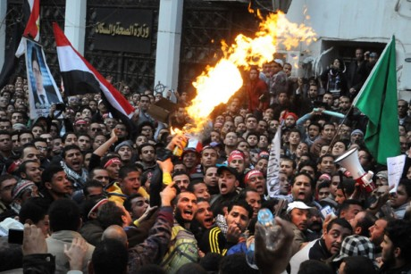 Egyptian protesters, left, spray burning aerosol over Muslim Brotherhood guards outside the Egyptian parliament.