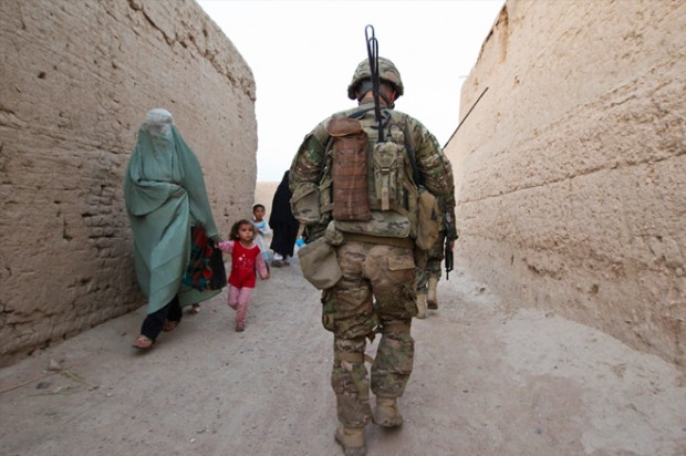 An Afghan family walks past a U.S. Army soldier in the town of Senjaray.