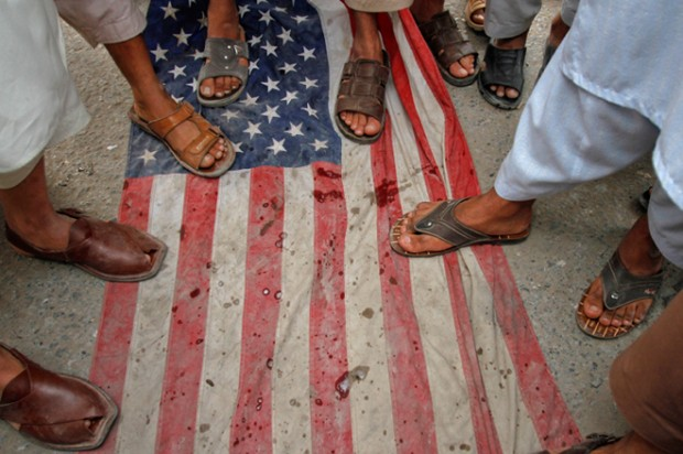 Pakistani men step on a U.S flag during an anti-American rally in Peshawar on April 13.