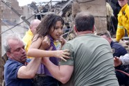 A child is pulled from the rubble of the Plaza Towers Elementary School in Moore, Okla., May 20, 2013.