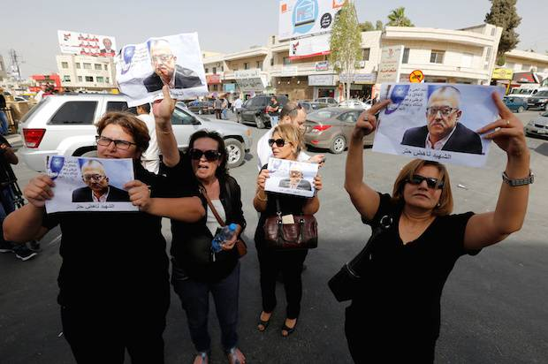 Relatives and friends of the Jordanian writer Nahed Hattar hold pictures of him during a sit-in in the town of Al-Fuheis