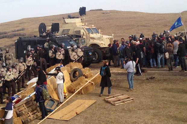 A line of police move towards a roadblock and encampment of Native American and environmental protesters near an oil pipeline construction site, near the town of Cannon Ball