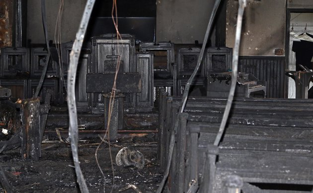 "Cables hang from the ceiling in the fire damaged Hopewell M.B. Baptist Church in Greenville, Miss., Wednesday, Nov. 2, 2016. ""Vote Trump"" was spray-painted on an outside wall of the black member church. Fire Chief Ruben Brown tells The Associated Press that firefighters found flames and smoke pouring from the sanctuary of the church just after 9 p.m. Tuesday. (AP Photo/Rogelio V. Solis)"