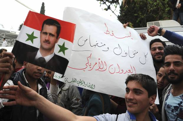 Syrian pro-government protesters hold a portrait of President Bashar Assad