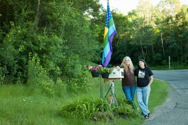 The author, left, and Wendy, with their flag at the end of their drive.