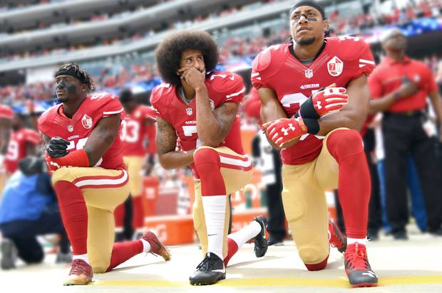 Eli Harold #58, Colin Kaepernick #7 and Eric Reid #35 of the San Francisco 49ers kneel during the anthem.